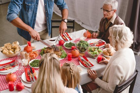 Photo pour High angle view of family members sitting at table and father cutting tasty turkey in Thanksgiving day - image libre de droit