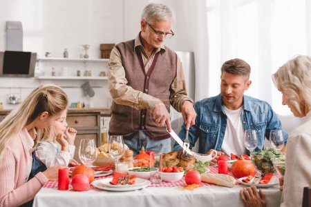Photo pour Family members sitting at table and grandfather cutting tasty turkey in Thanksgiving day - image libre de droit