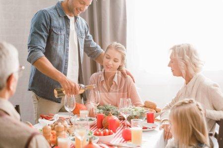 Photo pour Membres de la famille assis à table et père souriant versant du vin le jour de l'Action de grâce - image libre de droit