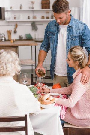 Photo pour Membres de la famille assis à table et père versant du vin le jour de l'Action de grâce - image libre de droit