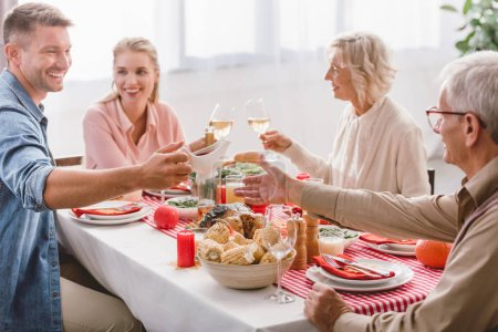 smiling family members sitting at table and clinking with wine glasses in Thanksgiving day