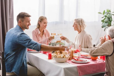 Photo pour Smiling family members sitting at table and clinking with wine glasses in Thanksgiving day - image libre de droit