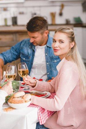 Photo pour Les membres de la famille souriants assis à table et serrant des verres à vin le jour de l'Action de grâce - image libre de droit