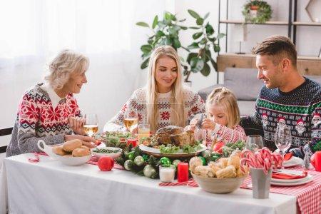 Photo pour Les membres de la famille souriants assis à la table pour célébrer Noël - image libre de droit