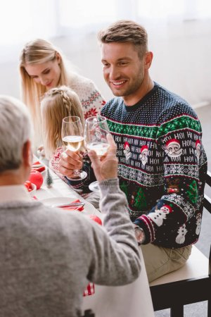 Photo pour Selective focus of family members sitting at table and clinking with wine glasses in Christmas - image libre de droit