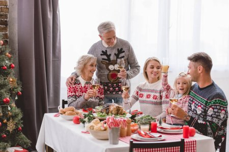 Photo pour Family members sitting at table and holding wine glasses in Christmas - image libre de droit