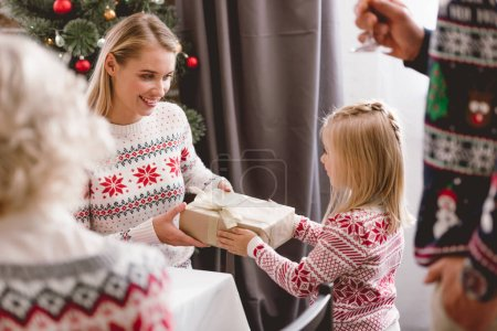 Photo pour Selective focus of mother giving christmas gift to her daughter - image libre de droit