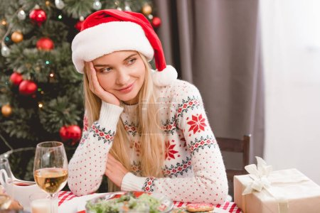 Photo for Attractive woman in santa hat and sweater sitting at table in Christmas - Royalty Free Image