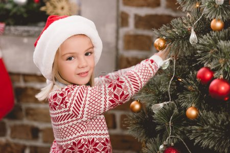 Photo pour Cute kid in santa hat and sweater decorating christmas tree - image libre de droit