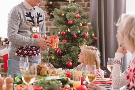 Photo pour Crochet vue du grand-père donnant un cadeau de Noël à sa petite-fille - image libre de droit