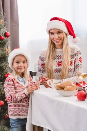 Photo pour Mère et sa fille en chandail et santa chapeaux souriant et regardant la caméra à Noël - image libre de droit