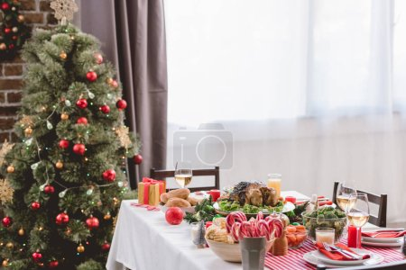 plate with tasty turkey, corn, candy canes, candles, gift and wine glasses on table and christmas tree