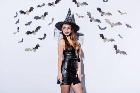 Photo pour Fille souriante en costume d'Halloween sorcière noire près du mur blanc avec des chauves-souris décoratives - image libre de droit