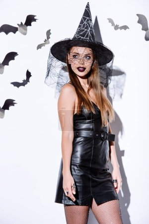 Photo for Girl in black witch Halloween costume near white wall with decorative bats - Royalty Free Image