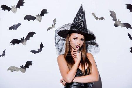 Photo pour Fille en noir sorcière Halloween costume regardant caméra près du mur blanc avec des chauves-souris décoratives - image libre de droit