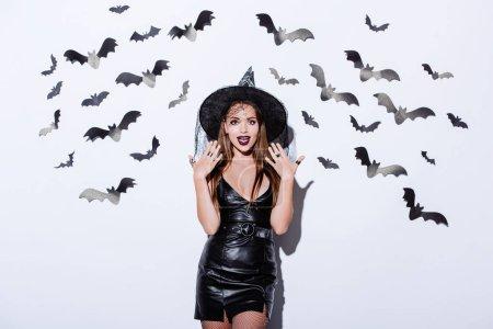 Photo pour Fille en noir sorcière Halloween costume avec bouche ouverte près du mur blanc avec des chauves-souris décoratives - image libre de droit