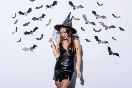 Photo pour Smiling girl in black witch Halloween costume near white wall with decorative bats - image libre de droit
