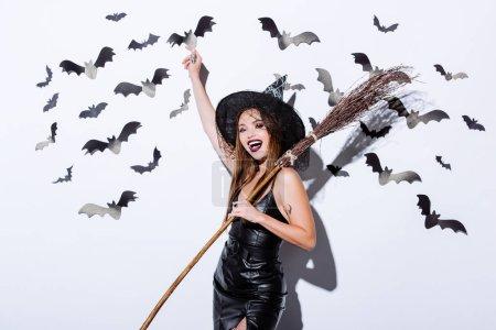 Photo pour Fille en sorcière noire costume d'Halloween avec balai près d'un mur blanc avec chauves-souris décoratives - image libre de droit