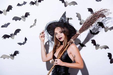 Photo pour Fille en noir sorcière Halloween costume avec balai près du mur blanc avec des chauves-souris décoratives - image libre de droit