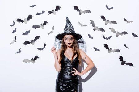 Photo pour Fille en noir sorcière Halloween costume près du mur blanc avec des chauves-souris décoratives - image libre de droit