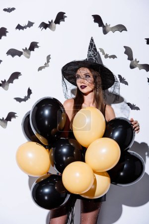 Photo pour Fille en noir sorcière Halloween costume tenant des ballons près du mur blanc avec des chauves-souris décoratives - image libre de droit
