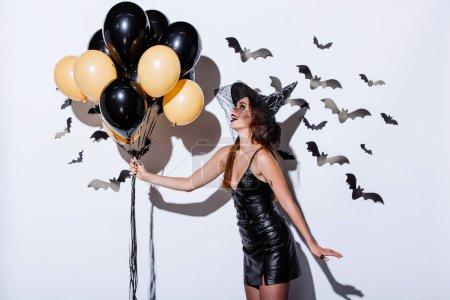Photo pour Happy girl in black witch Halloween costume tenant des ballons près d'un mur blanc avec des chauves-souris décoratives - image libre de droit