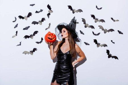 Photo pour Fille en sorcière noire costume d'Halloween tenant une citrouille fourmillante près d'un mur blanc avec des chauves-souris décoratives - image libre de droit