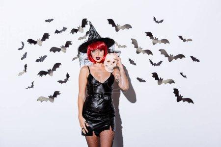 Photo pour Fille en noir sorcière costume d'Halloween avec des cheveux rouges tenant crâne près du mur blanc avec des chauves-souris décoratives - image libre de droit