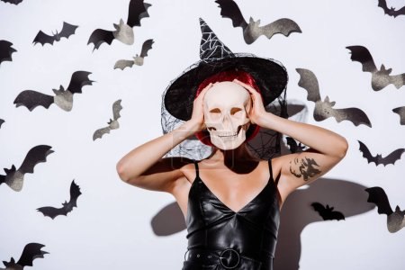 Photo pour Fille en sorcière noire costume d'Halloween avec des cheveux rouges tenant le crâne devant le visage près d'un mur blanc avec des chauves-souris décoratives - image libre de droit