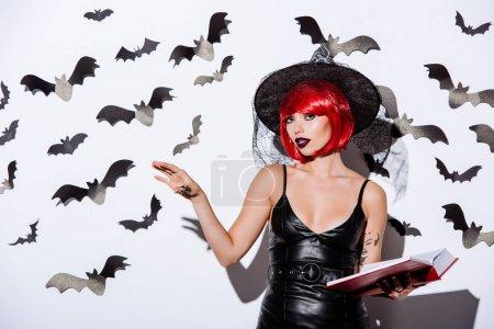 Photo pour Fille en sorcière noire costume d'Halloween avec des cheveux rouges livre tenant près du mur blanc avec des chauves-souris décoratives - image libre de droit