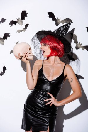 Photo pour Fille en noir sorcière Halloween costume avec des cheveux rouges regardant crâne près du mur blanc avec des chauves-souris décoratives - image libre de droit