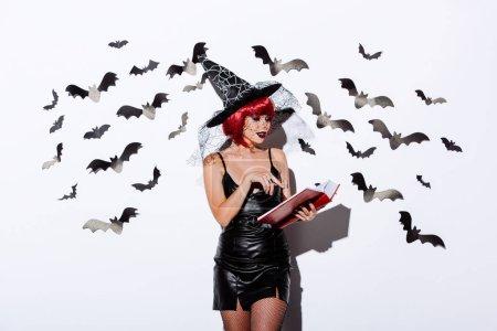 Photo pour Fille en sorcière noire costume d'Halloween avec des cheveux rouges livre de lecture près d'un mur blanc avec des chauves-souris décoratives - image libre de droit