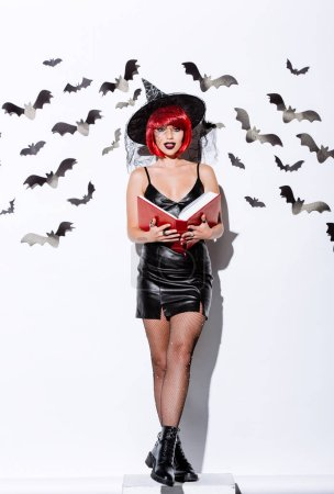 Photo pour Girl in black witch Halloween costume with red hair holding book near white wall with decorative bats - image libre de droit