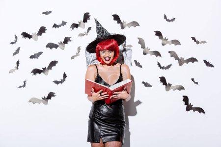 Photo pour Fille choquée en noir sorcière costume d'Halloween avec des cheveux rouges tenant livre près du mur blanc avec des chauves-souris décoratives - image libre de droit