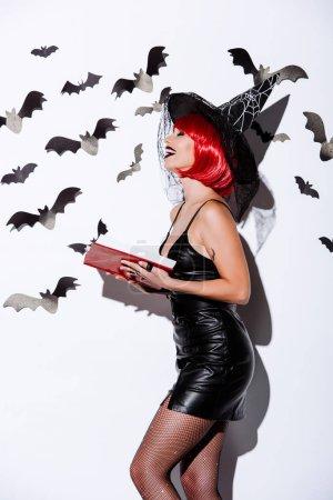 Photo pour Vue latérale de la fille riante en costume d'Halloween sorcière noire avec livre de tenue de cheveux rouges près du mur blanc avec des chauves-souris décoratives - image libre de droit