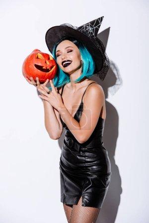 Photo pour Jolie fille sexy en sorcière noire Costume d'Halloween aux cheveux bleus tenant une citrouille sculptée sur fond blanc - image libre de droit