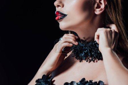 Photo pour Vue recadrée de fille vampire effrayant en robe gothique noire isolé sur noir - image libre de droit