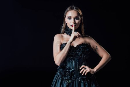 Photo pour Scary vampire girl in black gothic dress showing shh sign isolated on black - image libre de droit