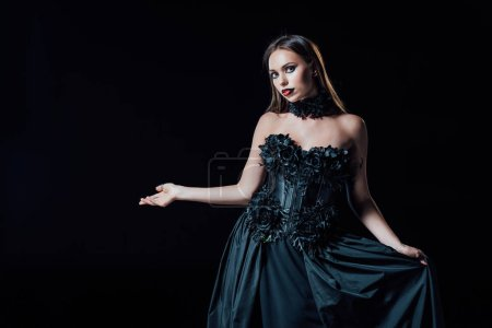 Photo pour Scary vampire girl in black gothic dress pointing with hand isolated on black - image libre de droit