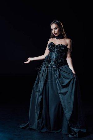Photo pour Effrayant vampire fille en noir gothique robe pointant avec la main sur fond noir - image libre de droit