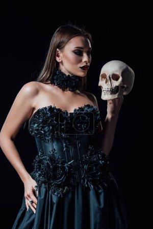 Photo pour Fille vampire effrayante en robe gothique noire tenant un crâne humain isolé sur noir - image libre de droit