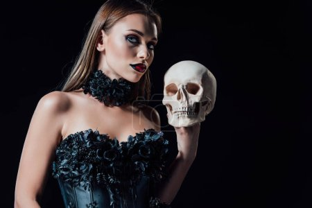 Photo pour Scary vampire girl in black gothic dress holding human skull isolated on black - image libre de droit