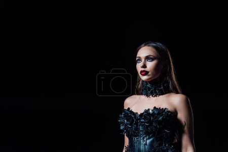 Photo pour Scary vampire girl in black gothic dress looking away isolated on black - image libre de droit