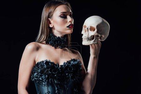 Photo pour Effrayant vampire fille en noir gothique robe tenant crâne humain isolé sur noir - image libre de droit