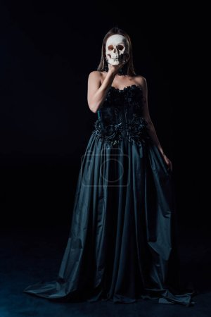 Photo pour Scary vampire girl in black gothic dress holding human skull in front of face - image libre de droit
