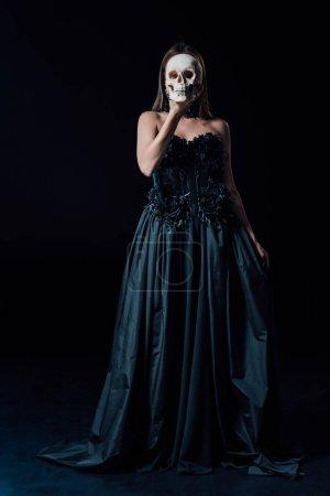 Photo pour Fille vampire effrayante en robe gothique noire tenant le crâne humain devant le visage - image libre de droit