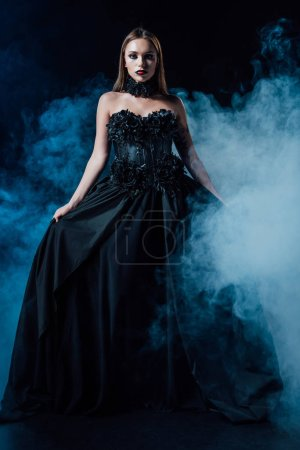 Photo pour Scary vampire girl in black gothic dress on black background with smoke - image libre de droit