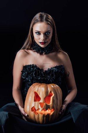 Photo pour Effrayant vampire fille en robe gothique noire tenant sculpté citrouille d'Halloween avec des bougies isolées sur noir - image libre de droit