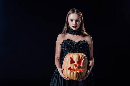 Photo pour Fille vampire effrayante en robe gothique noire tenant une citrouille d'Halloween sculptée avec des bougies isolées sur noir - image libre de droit