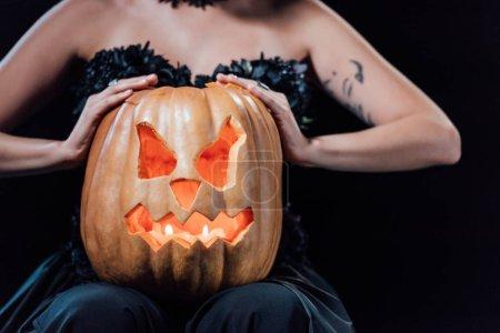 Photo pour Crochet vue d'une fille en robe gothique noire tenant une citrouille d'Halloween sculptée avec des chandelles isolées sur fond noir - image libre de droit